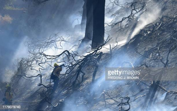 Firefighters work on a charred hillside near homes and the 118 Freeway in Simi Valley California on October 30 2019 after the socalled Yosemite Fire...