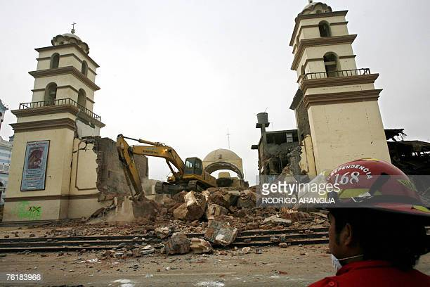 Firefighters work on a collapsed church 20 August 2007 in Pisco 250 km south of Lima after a massive 79magnitude earthquake rocked Peru 15 August...