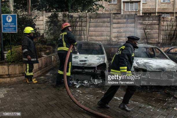 Firefighters work on cars that were damaged outside the Dusit Hotel on January 15 2018 in Nairobi Kenya A current security operation is underway...