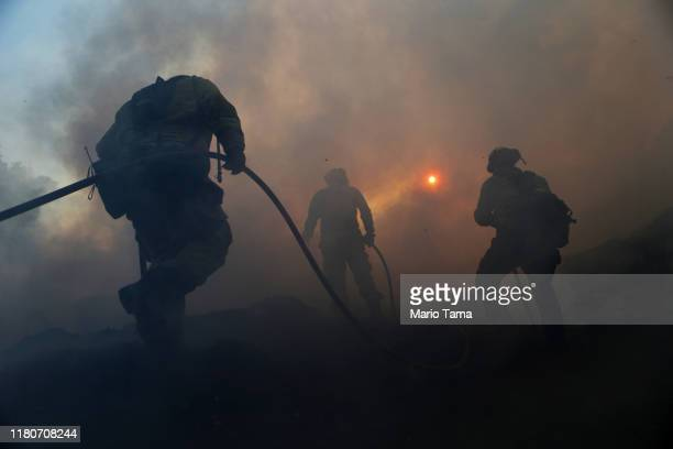 Firefighters work on containing a flare up at a mulch supplier during the Saddleridge Fire on October 12 2019 in Sylmar California The winddriven...
