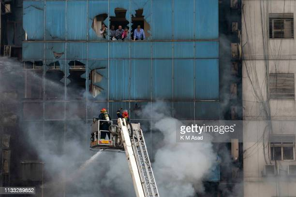Firefighters work on ladders to eclipse a blaze and try to rescue people in a building Banani. A huge fire split through an office building at least...