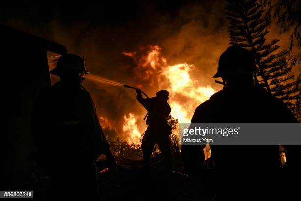 Firefighters work on structure protection as flames engulf a home next door on December 5 2017 in Oakview California