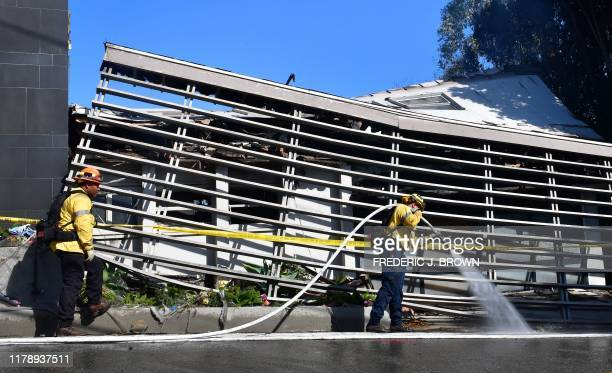 Firefighters work outside a destroyed home along North Tigertail Road near The Getty Center in Los Angeles California on October 29 2019 More than...