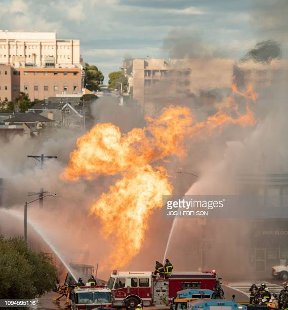 Firefighters work the scene as flames shoot into the air at an intersection in San Francisco California on February 6 2019 A gas line explosion in...