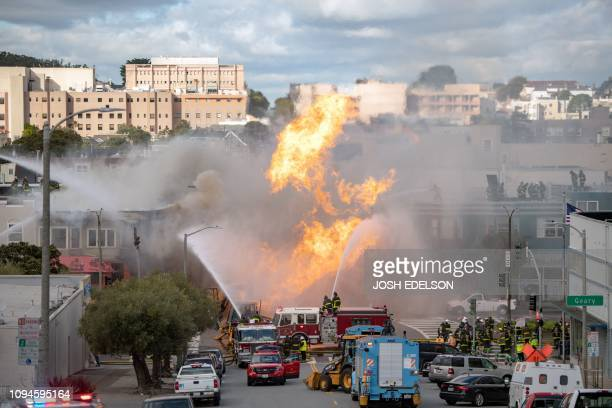TOPSHOT Firefighters work the scene as flames shoot into the air at an intersection in San Francisco California on February 6 2019 A gas line...