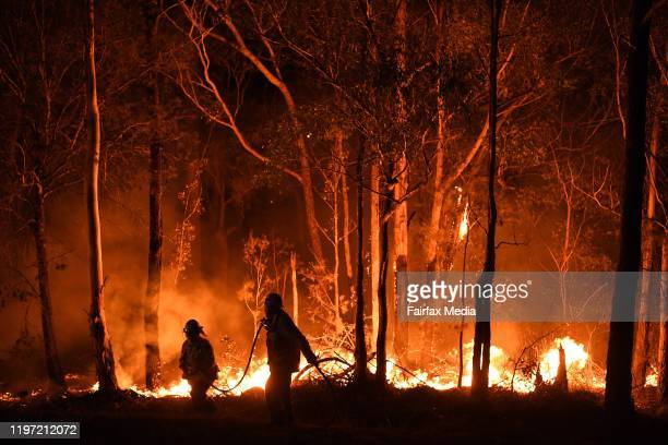 Firefighters work through the night to prevent a flare-up from crossing the Kings Highway in between Nelligen and Batemans Bay on January 2, 2020 in...