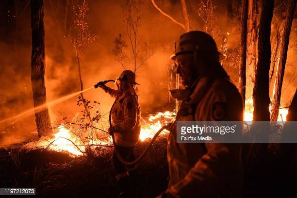 NSW RFS firefighters work through the night to prevent a flareup from crossing the Kings Highway in between Nelligen and Batemans Bay on January 2...