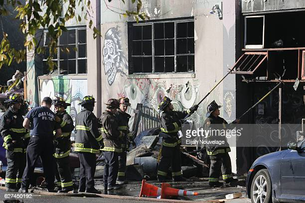 Firefighters work to clear the debris from a doorway following an overnight fire that claimed the lives of at least nine people at a warehouse in the...