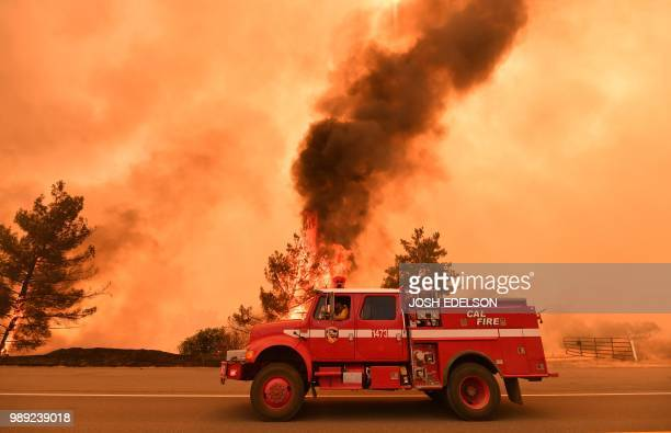 Firefighters work to control a fire as flames from the County Fire jump across Highway 20 near Clearlake Oaks California on July 1 2018 Californian...