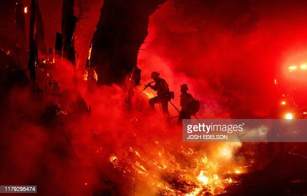 TOPSHOT Firefighters work to control flames from a backfire during the Maria fire in Santa Paula California on November 1 2019