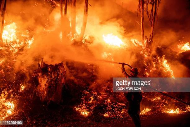 Firefighters work to control flames from a backfire during the Maria fire in Santa Paula California on November 1 2019
