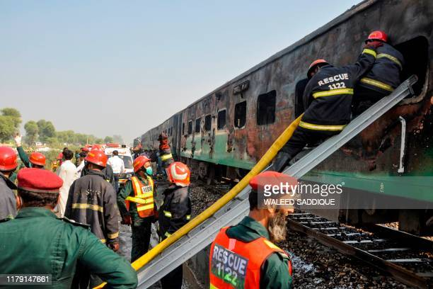 Firefighters work to cool down the burntout train carriages after a passenger train caught on fire near Rahim Yar Khan in Punjab province on October...