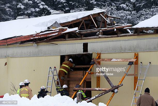 Firefighters work to cut a hole in the side of a barn in order to free the remaining two horses after a partial roof collapse at Flying High Stables...