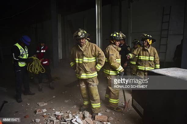 Firefighters work to demolish a damaged wall after a strong earthquake in Mexico City on May 8 2014 A strong 64magnitude earthquake rattled Mexico on...