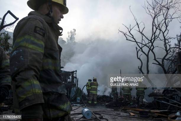 Firefighters work to extinguish a fire affecting two houses on a hillside at Camino Verde neighborhood in Tijuana, Baja California state, Mexico, on...