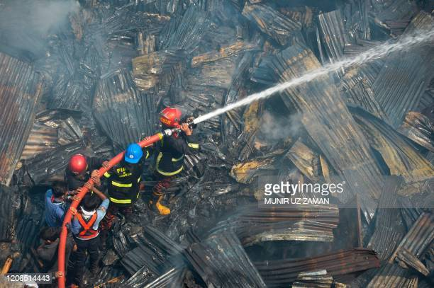 Firefighters work to extinguish a fire at a slum area in Dhaka on March 11, 2020.