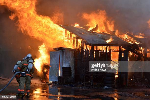 Firefighters work to extinguish a fire engulfing temporary homes for evacuees from the Fukushima Daiichi nuclear plant meltdowns on Oct 6 in the...