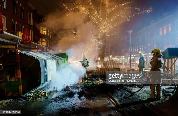 Firefighters work to extinguish a fire on the Groene Hilledijk in Rotterdam, on January 25 after a second wave of riots in the Netherlands following...
