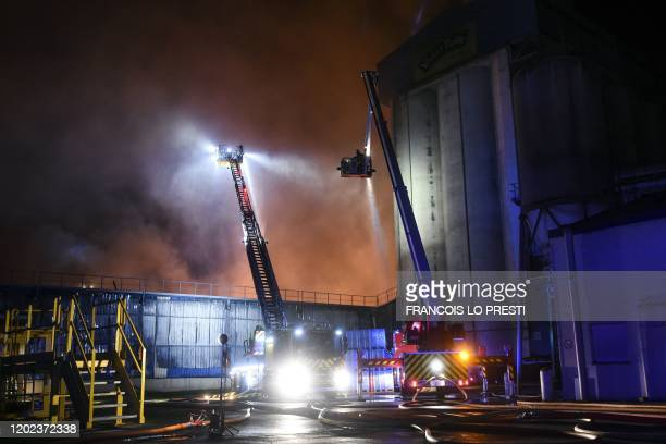 Firefighters work to extinguish a fire that broke out overnight at a grain processing factory belonging to the Soufflet Alimentaire group in...