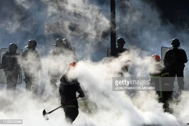 Firefighters work to extinguish burning waste as French gendarmes arrive for evacuation of the site as prison guards demonstrate and block the...
