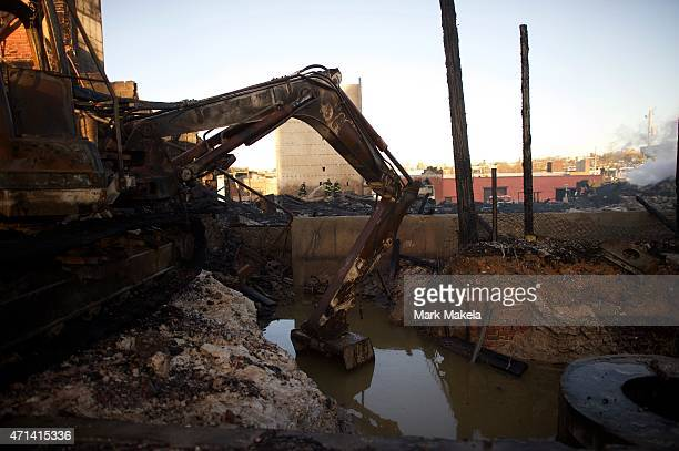 Firefighters work to extinguish the smoldering remains of a senior center set ablaze during night riots on April 28, 2015 in Baltimore, Maryland. A...