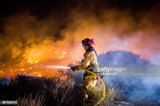 Firefighters work to extinguish the Thomas Fire as it burns past the 101 Highway towards the Pacific Coast Highway in Ventura California December 7...