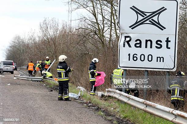 Firefighters work to pick up debris at the site where a bus crashed off the E34 highway near Ranst Antwerp province on April 14 2013 At least five...
