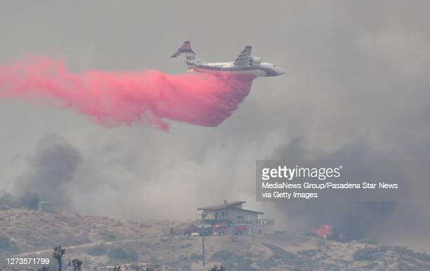 Firefighters work to protect a home as a tanker makes a phos chek drop high on a hill during the Bobcat Fire in Juniper Hills on Saturday September...