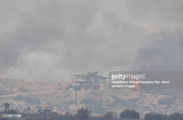 Firefighters work to protect a home high on a hill during the Bobcat Fire in Juniper Hills on Saturday September 19 2020