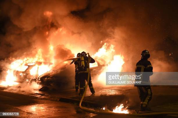 TOPSHOT Firefighters work to put out a fire as cars burn in the Le Breil neighborhood of Nantes early on July 7 2018 A French policeman who shot dead...