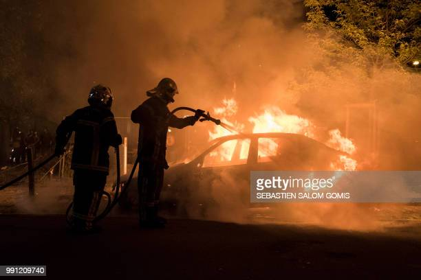 Firefighters work to put out a fire in a car in the Malakoff neighborhood of Nantes early on July 4 2018 Groups of young people clashed with police...