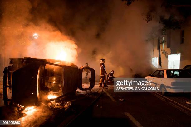 TOPSHOT Firefighters work to put out a fire near a burning car in the Malakoff neighborhood of Nantes early on July 4 2018 Groups of young people...