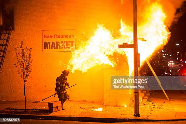 Firefighters work to put out a fire on the corner of Baker Street and N. Mount Street as protestors for Freddie Gray protest around the city in...