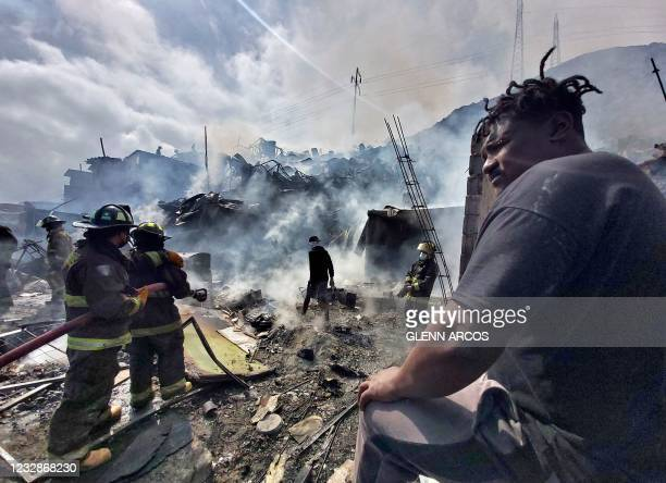 Firefighters work to put out a fire that affected dozens light material homes at two migrants' camps in Antofagasta, Chile, on May 13, 2021.