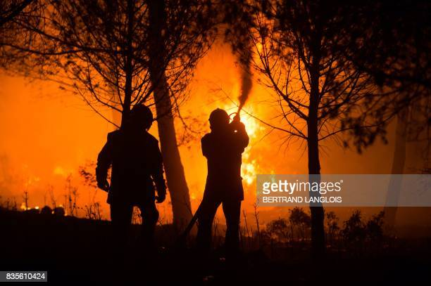 Firefighters work to put out a wildfire on a fire in CarnouxenProvence southeastern France on August 19 2017 Vacationers who were staying near...