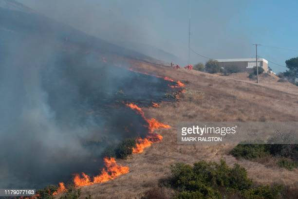 Firefighters work to put out flames on the road leading to the Reagan Library during the Easy Fire in Simi Valley California on October 30 2019...