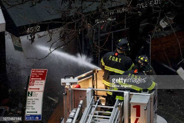 Firefighters work to put out the smoldering remains of an overnight fire that engulfed six businesses on Queens Boulevard December 13 2018 in the...