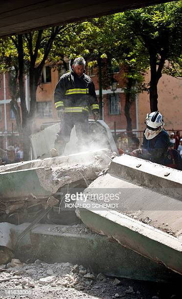 Firefighters work to remove a bus damaged by a bridge which collapsed following a strong quake that hit Mexico on March 20 2012 A powerful...