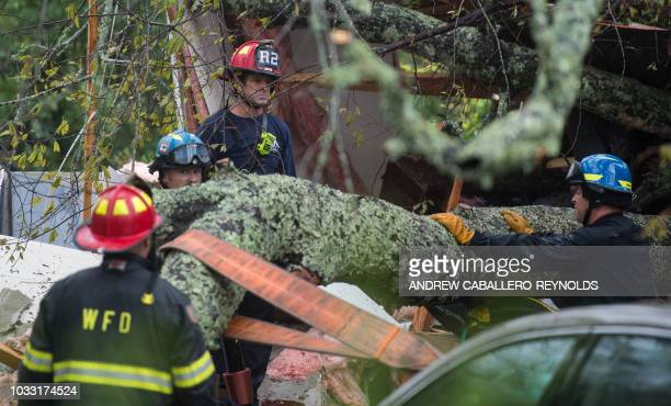 Firefighters work to remove a tree that fell on a house killing two residents during Hurricane Florence in Wilmington North Carolina on September 14...