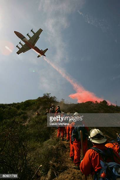 Firefighting air tanker drops phos-check fire retardant near firefighters cutting a line on a ridge in the steep and rugged terrain rising into the...