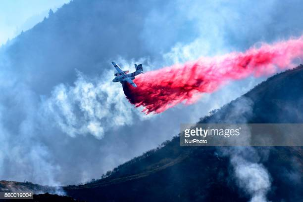 A firefighting air tanker makes a drop over a wildfire in Anaheim California on October 10 2017 14 helicopters 6 airplanes and over 1100 firefighters...