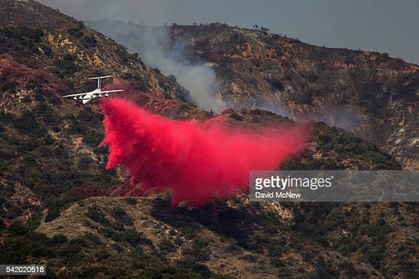 Firefighting aircraft drop fire retardant to protect communities that border the wildness in case evening winds change direction as is common in the...