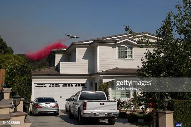 Firefighting aircraft drop fire retardant to protect communities that border the wilderness in case evening winds change direction as is common in...