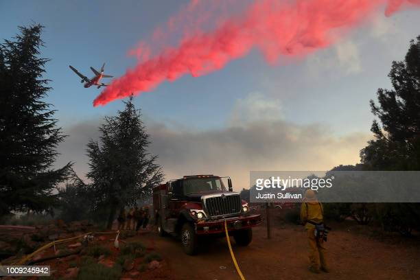 A firefighting aircraft drops fire retardant ahead of the River Fire as it burns through a canyon on August 1 2018 in Lakeport California The River...