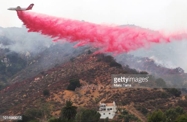 A firefighting aircraft drops fire retardant as the Holy Fire burns near homes on August 10 2018 in Lake Elsinore California The fire continues to...