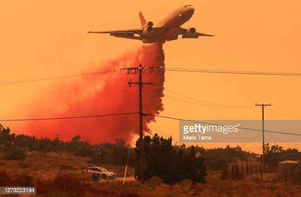 Firefighting aircraft drops the fire retardant Phos-Chek as the Bobcat Fire threatens nearby homes on September 17, 2020 in Juniper Hills,...