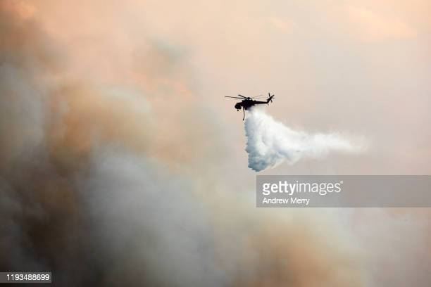 firefighting aircraft helicopter water bombing forest fires, bushfires in thick smoke at dusk, blue mountains, australia - nsw bushfires stock pictures, royalty-free photos & images