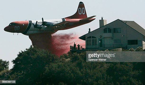 A firefighting airtanker drops fire retardant very near homes along West Camino Cielo Road community July 4 2008 The fire has doubled to 5400 acres...
