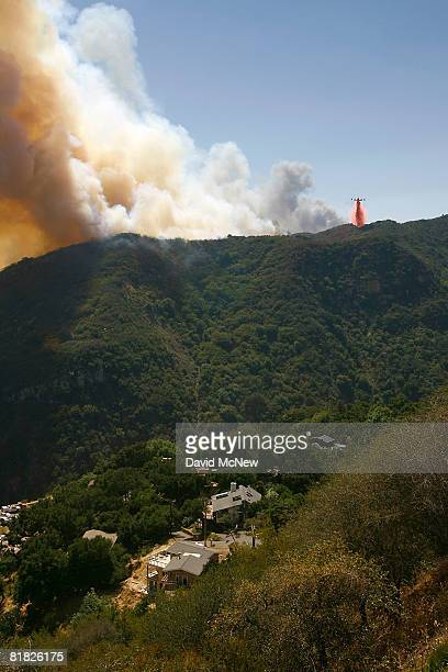 A firefighting airtanker drops PhosCheck fire retardant as the Gap fire which approaches homes that were rebuilt after being destroyed by wildfire in...