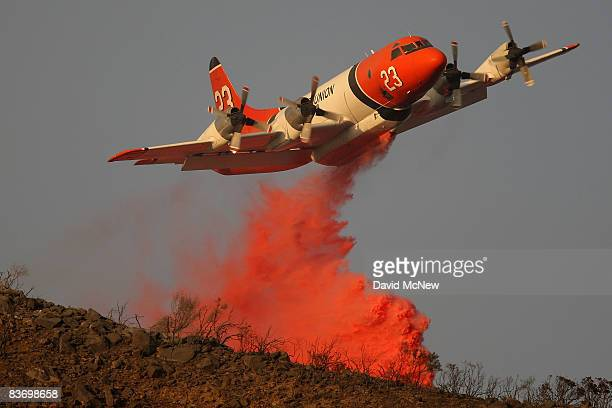 A firefighting airtanker drops PhosCheck fire retardant just before sunset in one of its final drops of the day to try to control the eastern flank...